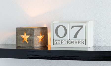 White block calendar present date 7 and month September on white wall background
