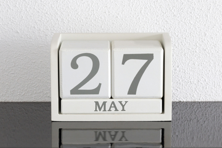 White block calendar present date 27 and month May on white wall background