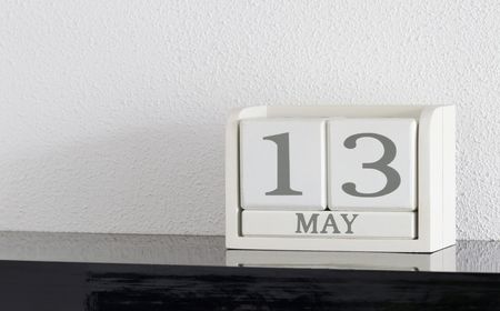 White block calendar present date 13 and month May on white wall background Stock Photo