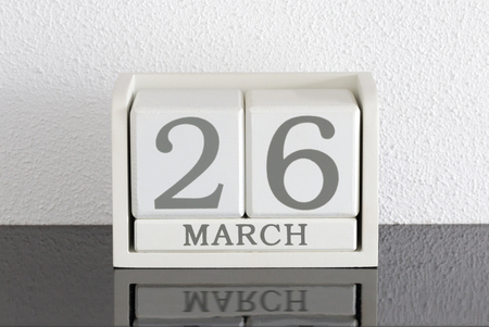 White block calendar present date 26 and month March on white wall background