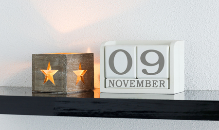 White block calendar present date 9 and month November on white wall background Stock Photo