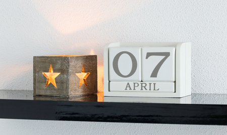 White block calendar present date 7 and month April on white wall background
