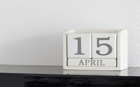 White block calendar present date 15 and month April on white wall background