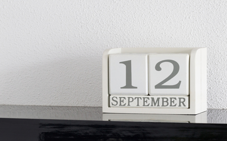 White block calendar present date 12 and month September on white wall background