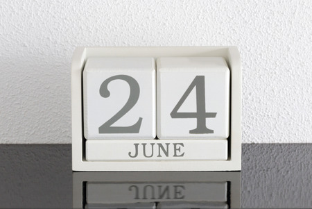 White block calendar present date 24 and month June on white wall background
