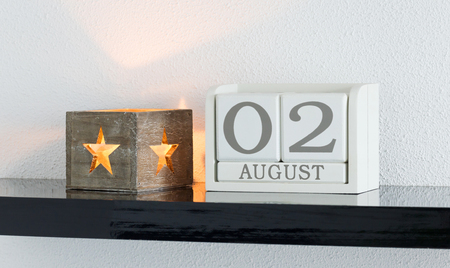 White block calendar present date 3 and month August on white wall background Stock Photo