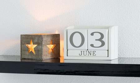 White block calendar present date 3 and month June on white wall background Stock Photo