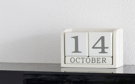 White block calendar present date 14 and month October on white wall background