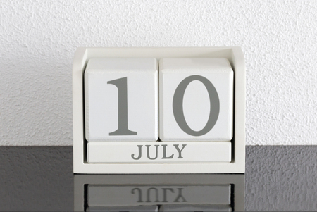 White block calendar present date 10 and month July on white wall background Stock Photo