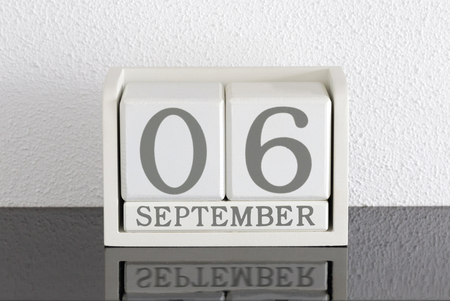 White block calendar present date 6 and month September on white wall background