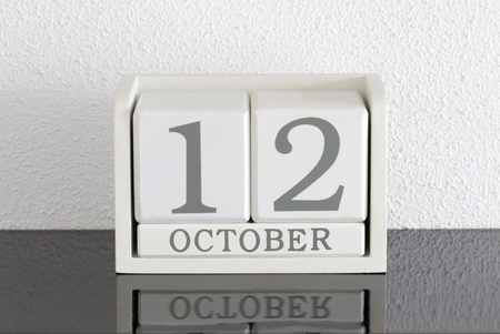 White block calendar present date 12 and month October on white wall background