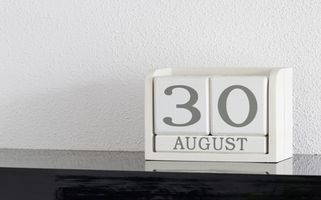 White block calendar present date 30 and month August on white wall background Stock Photo