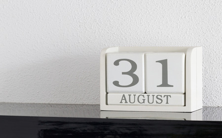 White block calendar present date 31 and month August on white wall background