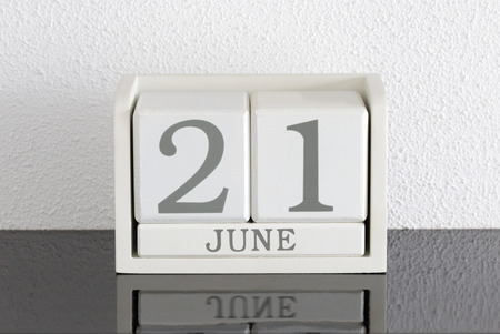 White block calendar present date 21 and month June on white wall background