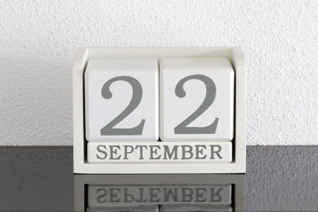 White block calendar present date 22 and month September on white wall background