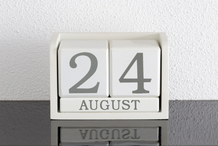 White block calendar present date 24 and month August on white wall background