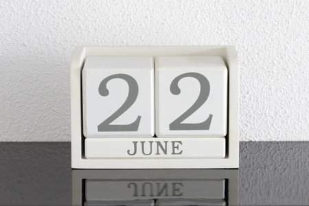 White block calendar present date 22 and month June on white wall background Stock Photo