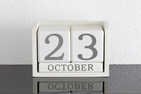 White block calendar present date 23 and month October on white wall background