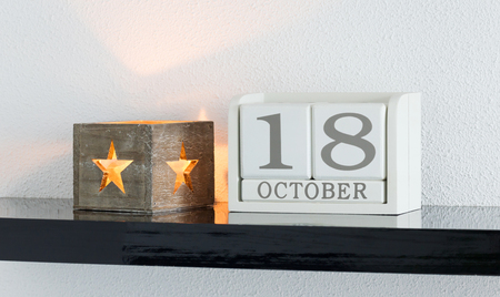 White block calendar present date 18 and month October on white wall background Stock Photo