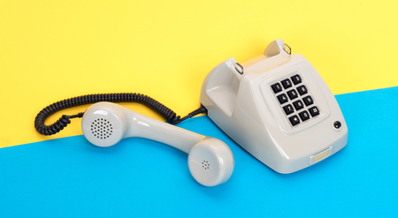 Vintage grey telephone with a colorful background Stock Photo