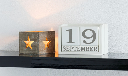 White block calendar present date 19 and month September on white wall background