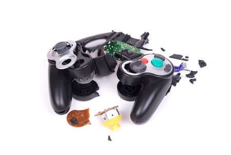 Broken video game controller on white background