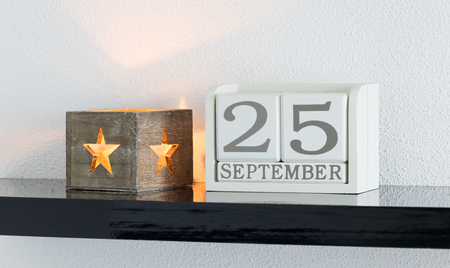White block calendar present date 25 and month September on white wall background