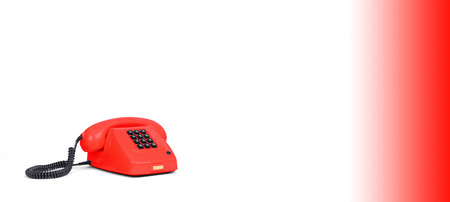 Vintage red telephone with a white background