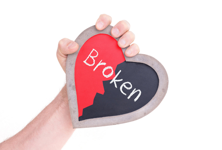 Adult holding heart shaped chalkboard - Isolated on white - Broken Stock Photo