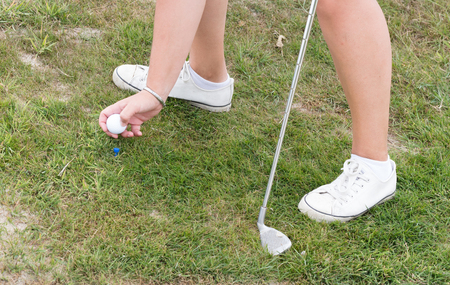 Golf ball on a golf track, woman playing