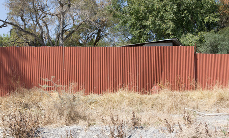 Red metal fence, protecting the property in Botswana