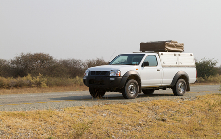 Pickup truck with rooftop tent driving in Botswana Foto de archivo - 114507447