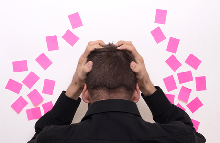 Businessman with pink sticky notes, isolated on a white background