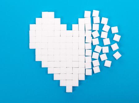 Broken heart made of sugar cubes lies on a blue background Stock Photo