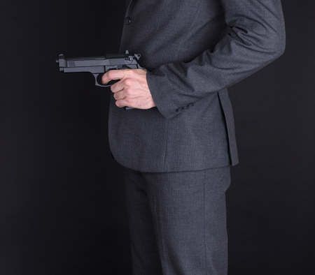 Man in suit with gun, isolated on black