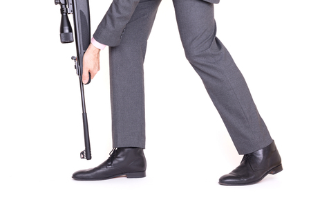 Concept - Businessman shooting himself in the foot with a rifle