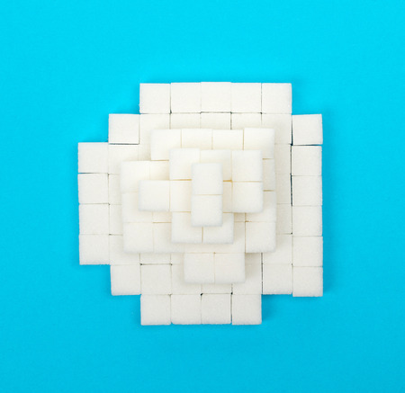 Pile of sugar cubes, isolated on blue