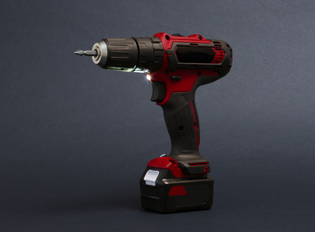 Cordless screwdriver or power drill isolated on a black background Imagens