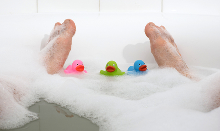 Men's feet in a bright white bathtub, selective focus on toes Banque d'images