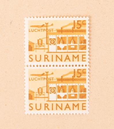 Suriname - CIRCA 1970: A stamp printed in Suriname shows a factory, circa 1970