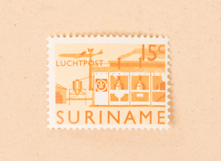 Suriname - CIRCA 1970: A stamp printed in Suriname shows a factory, circa 1970