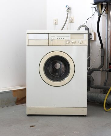 Old dirty washing machine on the attic, door closed