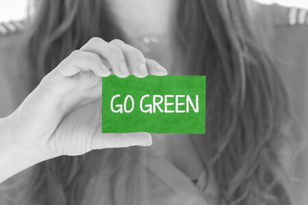 Woman showing a small message: Go Green