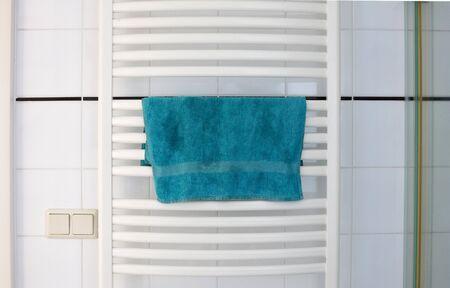 White metal heated towel rail set in the bathroom, dry blue towel Zdjęcie Seryjne