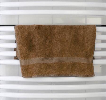 White metal heated towel rail set in the bathroom, dry brown towel