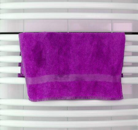 White metal heated towel rail set in the bathroom, dry purple towel Zdjęcie Seryjne