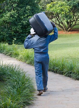 Man carrying a suitcase of a hotel customer - Selective focus