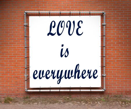 Large message written on white plastic, on a wall - Love is everywhere