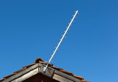 Simple old antenna on a roof, blue background