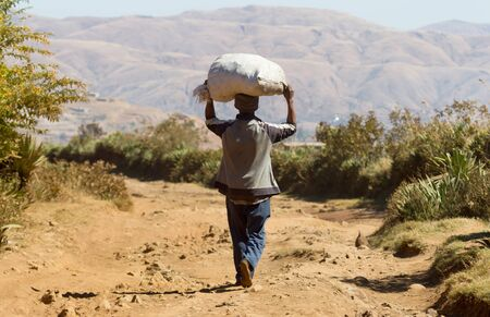 Young man walking on a bad road on Madagascar, Africa Banco de Imagens
